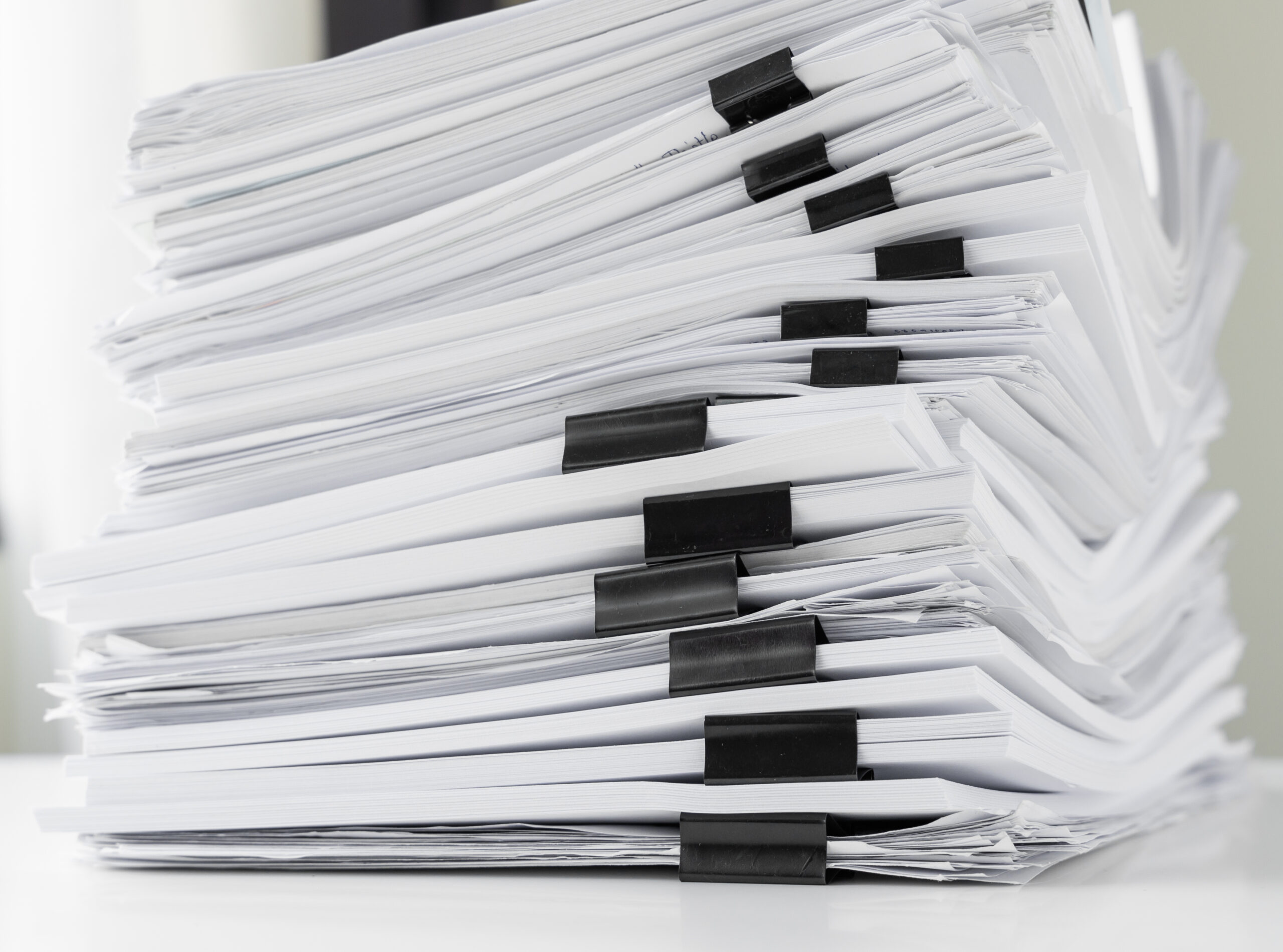 Piles of white papers work large piles of papers stacked together. On the desk in the office with black clip. Documents that are not finished. Business concept.